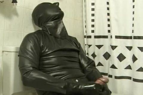 man In dark Latex Catsuit Jacks Off In bathroom